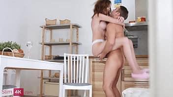Elle lit un livre dans la cuisine et est interrompue pour baiser